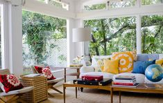 Fashion Designer Minnie Mortimer Lists Her Stunning Nantucket-Style LA Home // living rooms, Suzani pillows, yellow and blue pillows, teak side table, folding chair, Danish modern chair and table