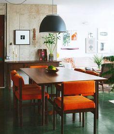 piso de ladrilhos hidráulicos verdes, cadeiras vintage com tecido laranja, parede de concreto... esse apartamento tem personalidade por todos os lados!!! ♥ pra completar, a sala totalmente integrada com a cozinha se abre para a cidade com grandes janelas (garantia de uma luz linda e uma vista tão bonita quanto) #decoração #modernista #todacasatemumahistoria #vintage (a matéria no blog chama: Modernismo revisitado)!!! foto: @lflorenzano