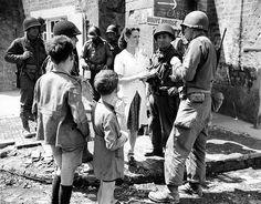 Red Cross volunteer, Marie-Esther Duchenes avec un groupe de soldats américains à la fontaine du village parle, deux enfants regardent la scène, à Sainte-Marie-du-Mont. (12.6.1944)
