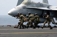 Speaker of the House, J. Dennis Hastert, and fellow members of Congress observe members of Explosive Ordnance Disposal Two, Unit Two Six simulates combat operations as they secure the flight deck during air power demonstration by Carrier Airwing THREE (CVW 3). The USS Harry S. Truman (CVN 75) and Carrier Airwing THREE (CVW 3) are currently on a six-month deployment in support of Operation Iraqi Freedom.   (US Navy Photo by: Photographer's Mate Airman Justin S. Osborne