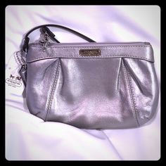 NWT Coach Wristlet NWT Brand New Coach Wristlet! Timeless silver metallic leather with rose lining. Perfect for a night out or a great gift idea! Measures approx 8 inches wide & 5 inches tall. This can fit either an iPhone 6s and probably 6s plus, lip gloss and credit cards.  Original retail hangtags are attached and the retail price has been removed from the hangtag, seen in pic. Happy shopping! Coach Bags Clutches & Wristlets