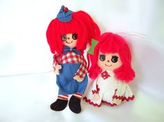 These vintage Christmas ornaments are just delightful! The yarn - haired Raggedy Ann and Andy have flocked faces with sticker eyes and drawn on mouths and noses. They are stuffed with a styrofoam ball and there are nylon hanging loops. Ann is wearing a white dress with red gingham check patches and red rick rack trim. She has a green bow in her hair.  Andy is wearing blue overalls, a red gingham shirt and has striped socks, black shoes and bendable wire legs.  She is 4 inches (10.2 cm)…
