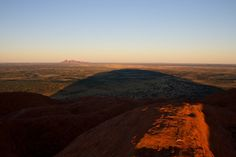 The monstrous shadow of Ayers rock being cast by the morning sun. Kata Tjuta (Olgas) sitting on the horizon Ayers Rock, Country Roads, Celestial, Mountains, Sunset, Nature, Travel, Outdoor, Outdoors