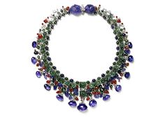 """Commissioned in 1936 by """"the world's most elegant woman"""" Daisy Fellowes, the Hindu Necklace sparked Cartier's Art Deco craze. Platinum, white gold, marquis and round old-cut diamonds, engraved sapphires, sapphire beads, square carved emeralds, emerald beads, emerald cabochon, leaf-shaped rubies, ruby beads, 13 briolette-cut sapphires (weighing 146.9 carats total) and two left-shaped carved sapphires (50.80 and 42.45 carats) adorn this Indian-style necklace."""