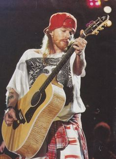 Axl Rose...a very rare photo of Axl playing a guitar.