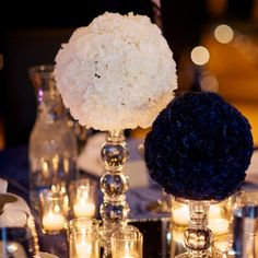 mini silk navy carnations placed them on a foam ball. The white pomanders were made of real white carnations. The pomanders were placed on glass candlesticks and placed on mirror squares to add a little silver and reflect the light from the candles.