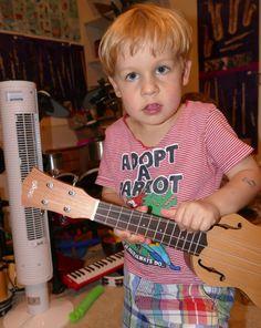 Arsène essaye un petit Ukulele au Tout Petit Conservatoire, la référence en éveil ludique pour les tout petits.