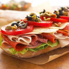 New Orleans-Style Muffuletta  Muffuletta is a Sicilian sandwich that originated in the French Quarter of New Orleans. We stayed true to its origins by stacking it with salami, ham, provolone, tomatoes, and a simple olive salad mixture.