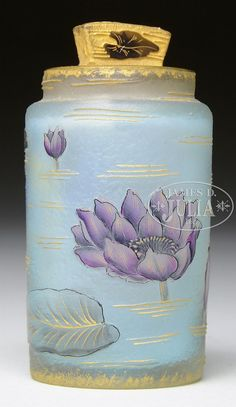 Daum scent bottle has cameo water lilies and lily pads surrounding the cylindrical body of the bottle.