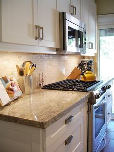 Sleek kitchen with white shaker cabinets, modern brushed nickel hardware, Kashmir White Granite Countertops and Venus Marble Mosaic in Milky Way backsplash  LIKE THE WORK TOP