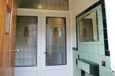Hal met groene tegels en glas in lood deuren in deze jaren '30 huis in Haarlem