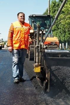 7400097 Young builder on Asphalting paver machine during Road street repairing works