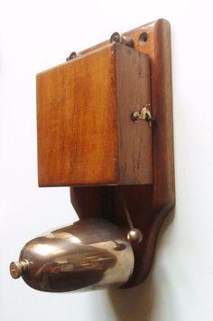 Original 1920's Electric Trembler Door Bell.  Mounted on a Mahogany back board, with removable box cover to access coils and adjustments. The back board has two countersunk fixing holes, a third has been drilled centrally below these, either as an additional fixing, or more likely to bring the wiring into the two terminals. These terminal have knurled brass screws for the connections.  The wiring is for a simple low voltage (9-12V) 2-wire system, power being provided by either a suitable… Door Bells, Covered Boxes, Wood Doors, 1920s, Drill, Door Handles, Third, Restoration, Two By Two