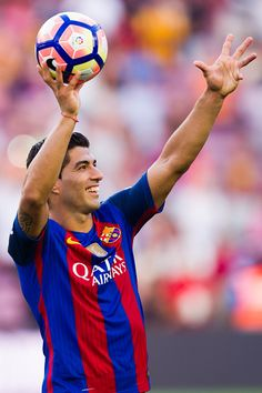 Luis Suarez of FC Barcelona shows the ball of the match as he leaves the pitch…