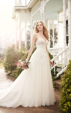 An illusion lace bodice is the hallmark of this flirty A-line wedding gown from Martina Liana. The tulle skirt catches the light with your choice of ivory or white beading. The back zips up under pearl buttons.