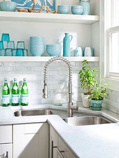 A high-arc faucet and serene blues and greens accent this classic white kitchen. See more photos from this home: http://www.midwestliving.com/homes/featured-mwl/beach-house-for-two-families/?page=5#