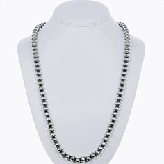 This Navajo Desert Pearl Necklace will wrap your neck in sheer luxury. A full length of Sterling Silver, 8mm beads were traditionally stamped & strung on heavy duty foxtail chain for a lifetime of wear. It measures 18 long & is dressed with Sterling cones & hook & eye. Native