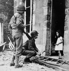U.S. Army soldiers talking to the only French girl left in Cerisy-la-salle, France after the Allied invasion of Normandy. July 25, 1944