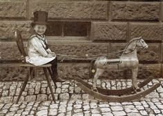 Little boy and rocking horse, Victorian era, is he playing at how to drive a carriage? A fine top hat, his sailor suit & rocking horse to play with all point to him being born into a family that had some money.