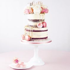Rose gold themed semi-naked birthday cake! Red Velvet and Belgian Chocolate tiers finished with a gold sequin drip, Rose Gold Prosecco macarons, large bloom white roses, bubblegum pink roses, gold cake pick and our Raspberry Chambord macarons in Blush and Rose Gold! LOVE the glittery rose gold ribbon trim too! #goldsequindripcake #goldsequindrip