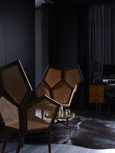 La Maison Champs Elysees, designed by Belgian fashion house Maison Martin Margiela  - A pair of caned honeycomb chairs in a moody bedroom