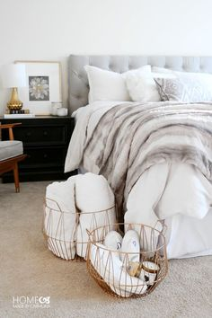 Creating a cozy bedroom with beautiful soft layers of bedding, padded headboard and a fur throw.  Add some chic wire baskets for essentials, a guest chair and you're set!