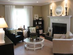 Tall pillar candles and white accents on the fireplace - large frame leaning on hearth