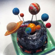 Solar System cake for my nephew's 6th birthday. Planets are edible (made by shaping rice crispy treats and covering with coloured fondant. Stars are mini silver cachous balls Sun was a chocolate orange. Milky Way bar and Mars bars at base were a hit with the kids.