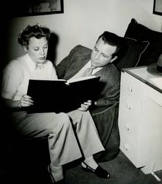June Allyson and Dick Powell look over a script while relaxing in his dressing room.