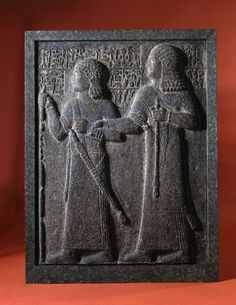 Cast of a Neo-Hittite relief depicting two figure walking to the left, the right hand one grasping the left wrist of the other with his right hand; Hittite hieroglyphic inscription around their heads and shoulders. 8thC BC (original)