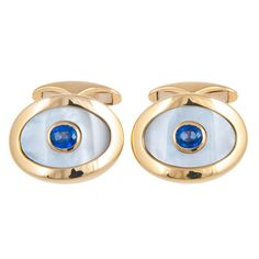 18ct Yellow Gold Sapphire Cufflinks  18ct yellow gold oval cufflinks set with mother of pearl and sapphire.  To be worn by the man with his own faultless style. This pair of yellow gold cufflinks, each set with a gently curved mother-of-pearl plaque with a central cabochon sapphire. Fitting his world perfectly, from Monte Carlo to New York, always the correct choice.