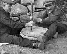 Grinding grain into flour with a quern stone, c1930s