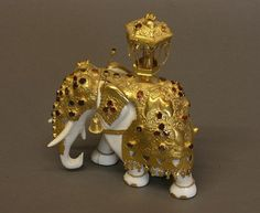 A Fine Indian Ivory, Silver Gilt and Garnet Set Elephant. Late 19th century. Surmounted by a small lantern. 17cm high. 12cm long. Some hairline cracks to feet. Small scratches to trunk   by The London Auction Rooms
