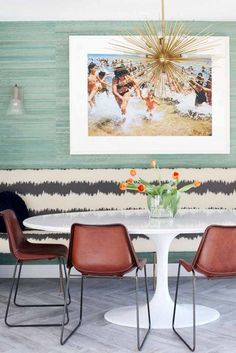 White round table, green wall, gold spike light, wall art, brown chairs, vase of tulips