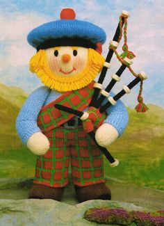 """Meet Great Uncle Angus from Jean Greenhowe's 'MacScarecrow Family' collection. An an adept bagpipe player he can be found wandering the hills of Sunnybogle on a warm summer's eve filling the air with lilting Scottish tunes... He is knitted with DK wool, is easy to make (although the bagpipes can be a bit fiddly) and is 34cm/13.5"""" tall. Designed and published by Jean Greenhowe Designs in 1991."""