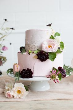Pretty pink buttercream wedding cake topped with fresh flowers