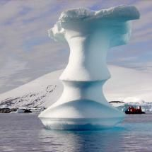 The Antarctic natural ice sculpture dwarfs 7 people in a Zodiac boat