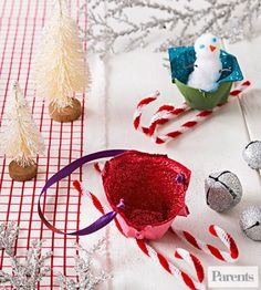 Cut cups from an egg carton, paint them, and sprinkle on glitter to create mini versions of Santa's sleigh. Chenille stems cut in half form the runners.