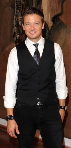 Jeremy Wearing White Button-Up Shirt With Sleeves Rolled Up, Shiny Black Tie and Black Vest and Pants With Watch on Left Wrist and Bracelet on Right Wrist
