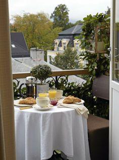 Den lille balkongen er rammet inn av grønne slyngplanter, og skaper en følelse av å sitte på en hotellbalkong ved Middelhavet.