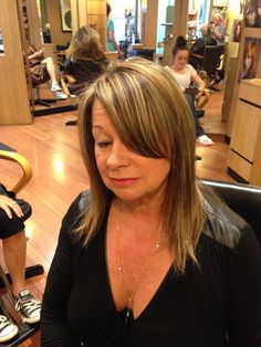 Brown hair with natural highlights cut into a long layered hair style with along side swept bang