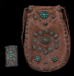 A Navajo bow guard and leather bag decorated with jewelry items
