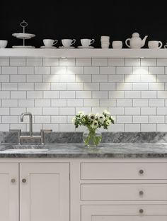 Classic base cabinets in matt lacquer Farrow & Ball Strong White with 'Dot' handles in brushed nickel and worktop in 30mm White Fantasy leather. Splashback: white metro tiles Minton Hollins White.