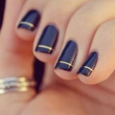 Shiny, navy polish with a thin gold strip gives edgy elegance to @Maison Jules' nails.