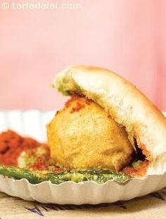 """Vada Pav: Mumbai's very own burger. The vada is made of a spicy potato filling deep fried in a gram flour batter. Along with a hot and spicy garlic chutney, it is served inside a small """"Laddi Pav"""". Yummy Snacks, Snack Recipes, Cooking Recipes, Yummy Food, Potato Recipes, Indian Snacks, Indian Food Recipes, Vegetarian Recipes, Curry Recipes"""
