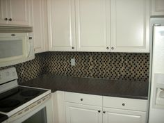 good contrast between the light colored cabinets and the darker glass tile backsplash