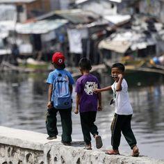 Tre bambini filippini camminano su un muro a Bacoor. Secondo Armin Luistro, segretario del Dipartimento della pubblica istruzione, il governo sta introducendo nelle scuole un libro sulla prevenzione delle calamità, per migliorare le capacità di comprensione dei bambini di catastrofi naturali e artificiali