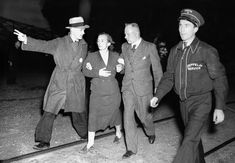 An unidentified woman survivor is led from the scene of the Hindenburg disaster at the U.S. Naval Station in Lakehurst, New Jersey, on May 6, 1937