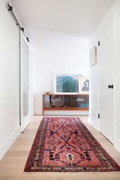 a whitewashed entryway with a red vintage runner