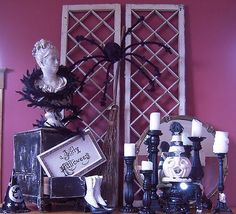 A pair of trellises, black candlesticks, a broomstick, and a spider for a vintage-style Halloween vignette.